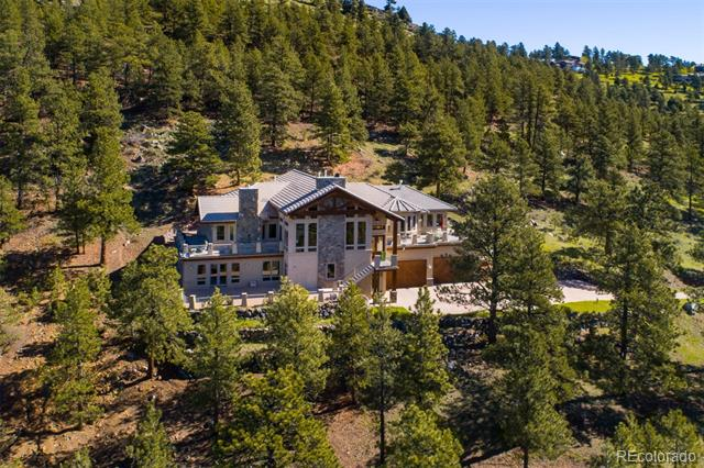 """Genesee jewel sparkles in its perfection & allure on a south-facing hillside offering expansive views from snow-capped Mt. Evans to Denver city lights.  Sunrise to sunset, you will love the privacy & silence from multiple outdoor living areas. 6 car garage & main level living enhanced by elevator access, freshly redone hickory floors in 3"""", 4"""" and 5"""" planks, immense rock gas fireplaces; exposed post & beams, slate & travertine floors +slab stone countertops thru-out.  Gourmet kitchen, ideal for entertaining, opens to the great room & features double slab granite islands, knotty alder cabinetry, walk-in pantry, vegetable sink & stainless appliances:  Wolf double ovens + 5-burner gas cook top/hood, 2 Kitchen-Aide dishwashers, trash compactor & 2 microwaves.  Fabulous master has private deck, wet bar, gas stone fireplace & luxury bath with steam, jetted tub & huge walk-in closet.  2nd main level Mother-in-law suite or den.  Walk-out level has 3 bedrooms, media, family room & flex space."""