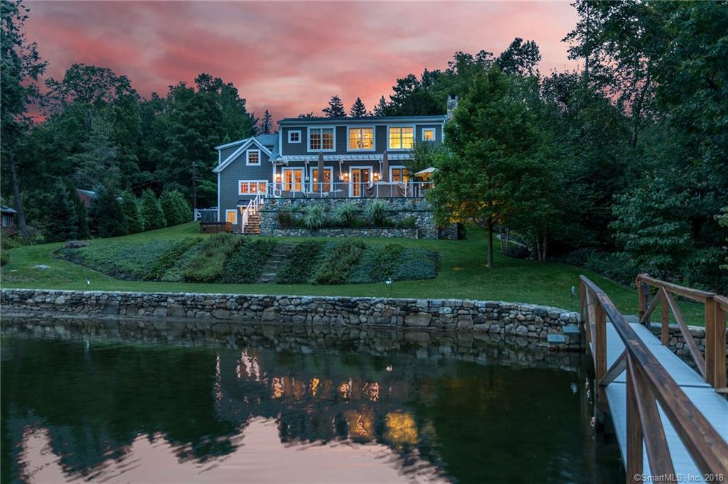 """125' DIRECT LEVEL WATERFRONT-Western Exposure w/intoxicating Views by night & inspiring mtn vistas by day. Security Gate w/state of art interior/exterior home automation system.A stone-lined babbling brook in side yard leads to magical place of sunlight & shadows, shimmering leaves & bubbling water. The 600 sq ft bluestone patio w/full outdoor kitchen w/pergola, double thick granite counters overlooks a sprawling lawn (irrigation system w/remotes), colorful professional landscape & path to oversized custom cool surface Dock & swim platform w/2 sets of stone steps from sea wall to lake. Style & sophistication w/open floor plan for modern living. One BRIGHT idea after another is used in this energy efficient home w/a touch of classic New England character.Designed for easy living & entertaining in & out. Majestic windows allows light to stream into Great Room & Open Dining Areas. Kitchen is an epicurean's delight. Main level Office can double as an additional Bedroom. UL hosts Private Guest Wing, Bonus Room and Master Suite w/its fitted walk-in wardrobe & sumptuous spa bath including whirlpool tub, steam shower & sauna. Finished LL w/game room & private entry walkout allows for additional living space or bedroom. 5"""" white oak floors/Radant heated flrs on ML & UL.Lutron electric shades thruout. Heated Garage w/rubber floor.HydroAir-5 zone w/Buderous burner/20KW generator. A property for people who know & want quality! We can float your boat!"""