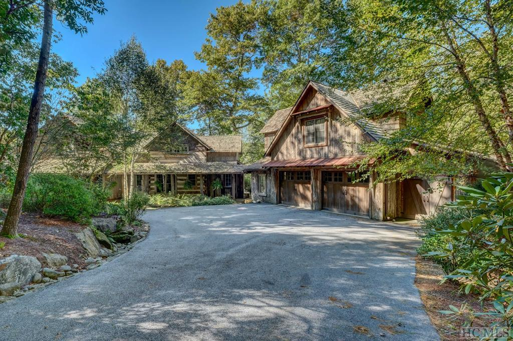 This masterpiece of an antique hand-hewn Log, stone and wood home sits on 2 plus acres with a stream running through the property that overlooks a very nice sized pond. The home is of the true quality of a craftsman with much detail throughout. The main house was constructed from 2 antique log homes that are 100+ years old. The Master Bedroom and his & her Master Baths, with walk in closets, are on the main floor. Access to a large porch with a beautiful stone, wood burning fireplace will allow you to sit and enjoy cool Spring and Fall Nights. The family room also has an extra large, magnificent, wood burning fireplace. This is a spacious home with MANY upgrades throughout and a loft, additional living area with a large bedroom and full bath. In addition, just a short stroll from the main house, tucked in the trees on a creek is a one bedroom/one bath hand-hewn log guest cabin with a kitchenette, living room with its own wood burning fireplace.  both structures have encapsulated basements for your storage needs.  The main house has a large 2 car garage addition with a playroom / bedroom and a half bath as well as a cart barn attached. Also on the property is a custom Tree House built out of antique lumber that is accessed by a footbridge over the creek. This is an incredible, private, well-kept property that is nestled close to Panthertown Valley with over 6,000 acres of Nantahala National Forest. this home also is granted access to the Chiquapin Development amenities including: biking and hiking trails, golf practice range, fishing, and many other activities. You will not find another quality craftsman log home like this in the entire GLENVILLE/CASHIERS area.