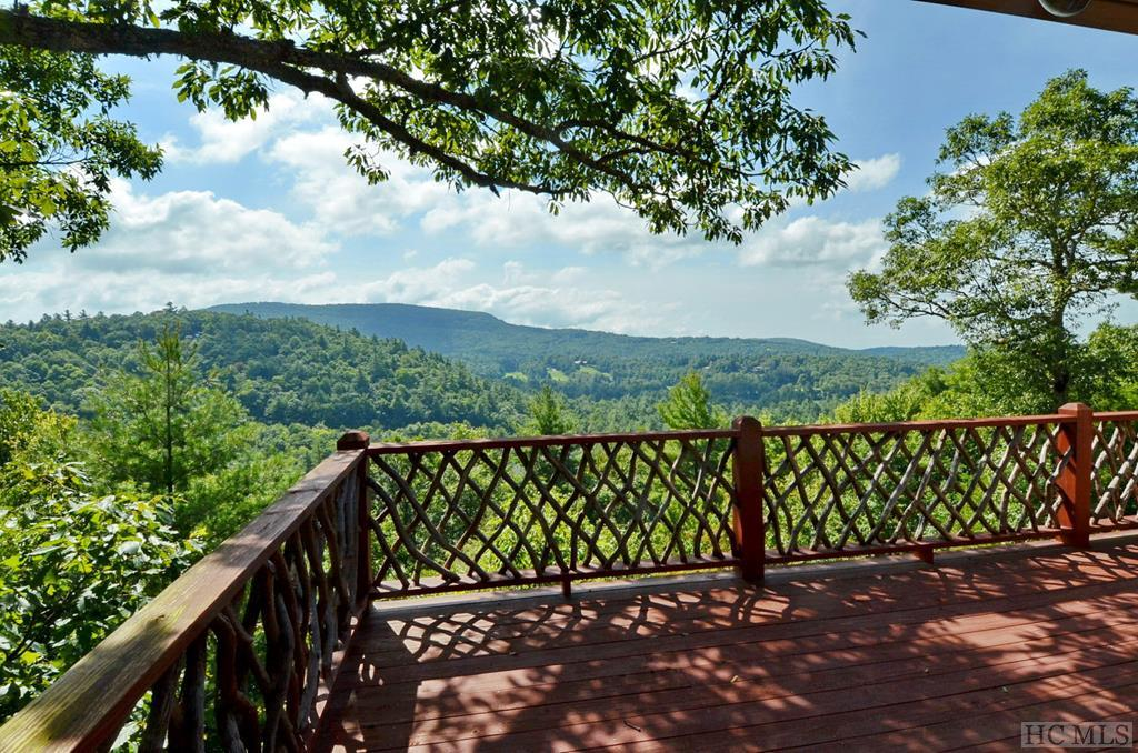 This renovated four bedroom, three bath home sits at the very top of the gated Cowee Ridge community, with stunning 180-degree, long range mountain views and Wildcat Cliffs Country Club in the distance. Enjoy peace, privacy and cool temperatures at an elevation of over 4,000 feet, in one of the best locations the area has to offer. Cowee Ridge is midway between Highlands and Cashiers — the crossroads in Cashiers and Main Street in Highlands are both just eight minutes from the entrance. A major remodel in 2006 included an all-new kitchen, new heating and air conditioning, a new roof, raised ceilings and new bathrooms on the main level, and all new hardwoods. Plenty of indoor and outdoor living space makes entertaining family and friends a pleasure. Reduced $100,000--priced to sell and now includes all furniture. Close, and start enjoying life in the mountains right away.