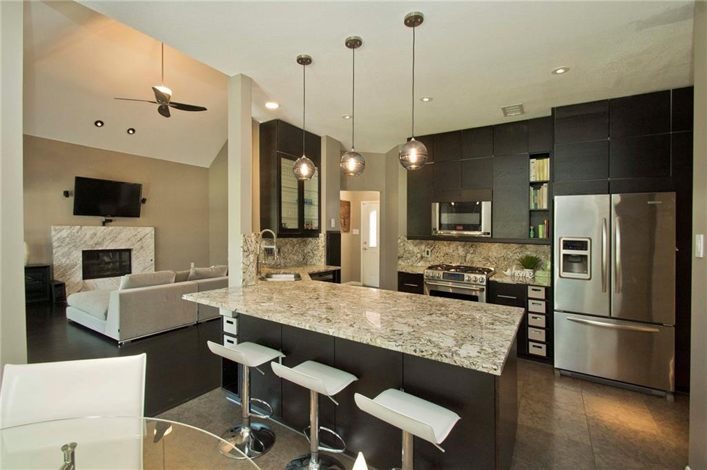 Modern updated kitchen has huge breakfast bar granite counter, stainless steel appliances, pendant lighting and more! Glass door cabinets and built in shelves add interest and character to this kitchen!