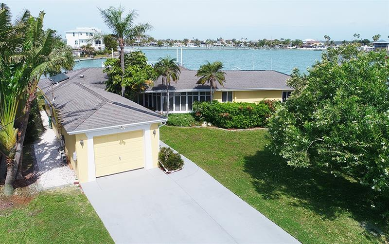 A rare find!  This home sits on a wide  open -panoramic- 155 ft. waterfront (1/4 acre). w/  dock and 2 decks. Enjoy Boca Ciega Bay while inside/ outside home or walk to  Gulf's white sandy beaches & meet neighbors for Sunset. Active community w/parks/fitness/playground. Also - double lot  big enough to build your spectacular new mansion!  Don't miss!