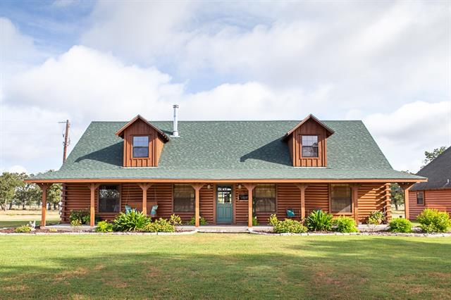 Distinctive log home, well-maintained acreage, oak trees, pond. Main house: vaulted ceilings, open concept living, dining, kitchen. Large porches. Master suite: double vanity, tub, shower & walk-in closet. Guest house (576 sqft), attached to 3-car carport, includes kitchen, living, 1 bed, 1 bath. Updates to main house completed 2017-2018: carpet, granite counters, roof, A/C unit, fresh paint, & re-stained/sealed exterior logs. Additional 1 - 35 acres available, $8K per acre. 2 additional ponds available.