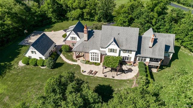 """Custom French Country-styled home by the acclaimed Mitchell Wall Architecture and Design who are known for luxury homes with quality design & finishes. Located on 9 acres in Labadie's most sought-after neighborhood. Easy access to I-44. Only 10 minutes from beautiful Washington, MO. This home showcases exceptional design rarely seen in newly built homes: custom 2"""" thick Mahogany front door with leaded glass sidelights, double barrel vaulted entry ceiling, stunning 3 level circular stairway and vaulted ceilings with hand distressed Douglas Fir beams. The designer kitchen opens to the Dining Room & Hearth Room. The cabinets were custom made by local craftsmen. The Great Room has a custom wrought iron chandelier, wood-burning fireplace & a vaulted beamed ceiling. Sliding glass doors that lead to the back patio with a pergola & wood-burning fireplace. The lot is partially wooded & well suited for horses. 2-car attached garage & a detached 2-car garage. Geothermal heating. Charter internet."""
