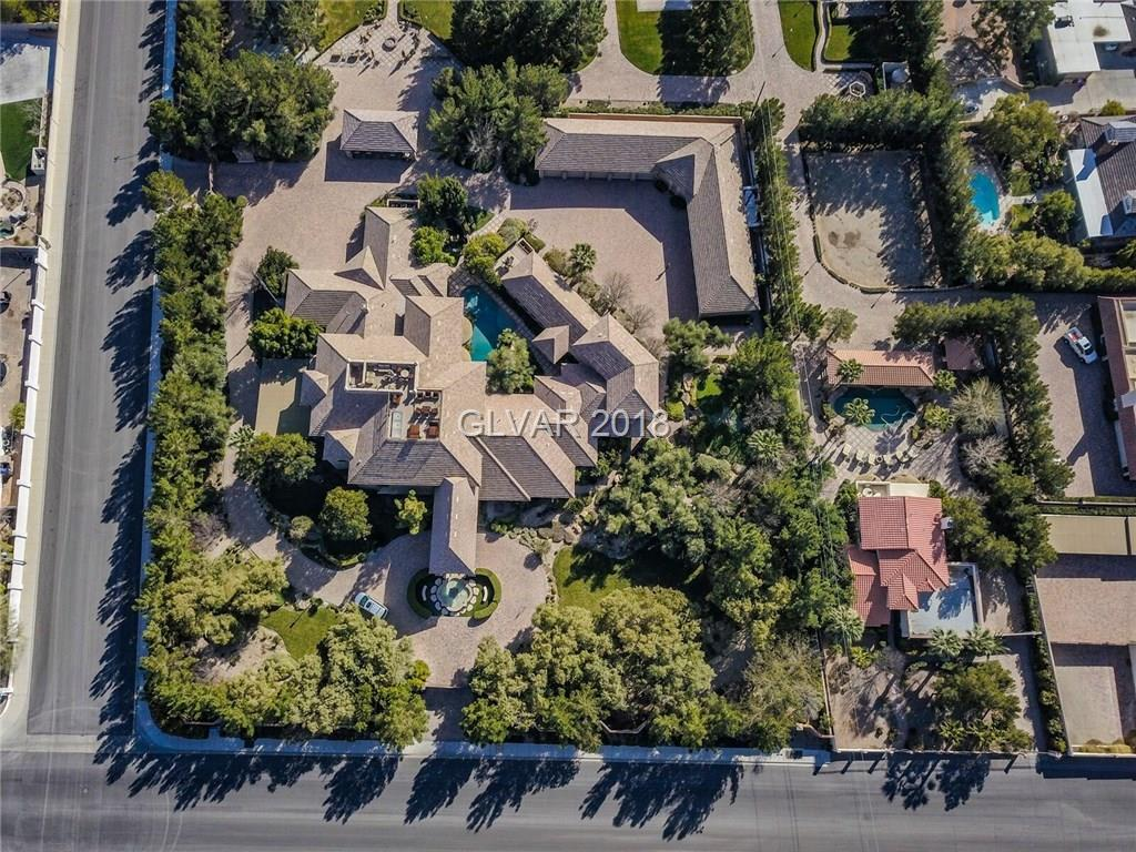 A true one of a kind compound in the heart of Las Vegas *gated/guard house for ultra privacy. This masterpiece has 4 separate parcels totaling 6.8 acres *10+ car garage *indoor pool *media room *game room *rooftop deck with 360° view *massive master includes seating room and an ultimate wet bar *outdoor resort style pool *tennis court *batting cage *2 additional homes that encompasses 2765 sq.ft. and 5478 sq.ft. plus a 2.18 acre park like parcel*