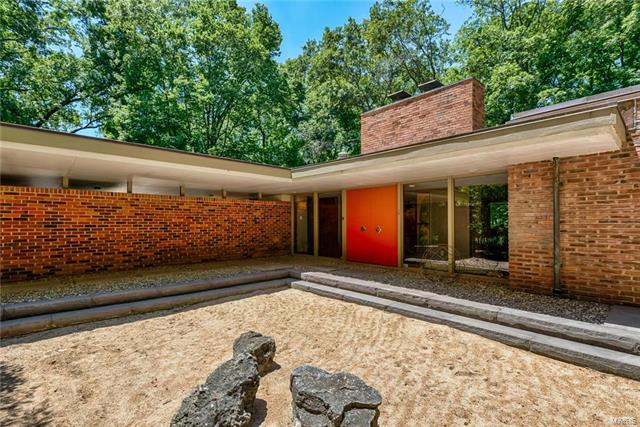 Located on 3 private acres in Ladue is this Bernoudy-design contemporary masterpiece. The centerpiece of the home is an open Living Room & Dining room with vaulted ceilings, coved lighting, built-in bookcases, a fireplace & an expanse of windows that look onto a wooded lot. The kitchen is bright & features granite counters, double ovens, stainless steel refrigerator & skylights. The master bedroom suite is special with a dressing room that would satisfy anyone with a need for plenty of closet space. The master bath has been renovated with a soaking tub, walk-in shower, custom finishes & marble tile. Adjoining the master bedroom is another area with an expanse of closets & another full bath. There is a cozy den with a fireplace on the main floor, laundry & office. The LL has a full wall of windows & sliding doors that lead to a terrace. There is a large recreation room with a wood-burning fireplace, 3 more bedrooms, 2 baths, new kitchenette, storage & a 2nd laundry.
