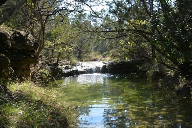 7.2 acres of hill country heaven!  With a grove of live oak trees for privacy from the road, this beautiful, rolling property with wet weather creek and pond has two swimming holes with waterfalls to enjoy several months of the year.  Choose from multiple sites to build your dream home on this incredible property, or potentially subdivide (minimum 3 acres) with the creek in between.  Multiple structures on-site could serve as storage and guest houses, and offer flexibility to live in while you build.