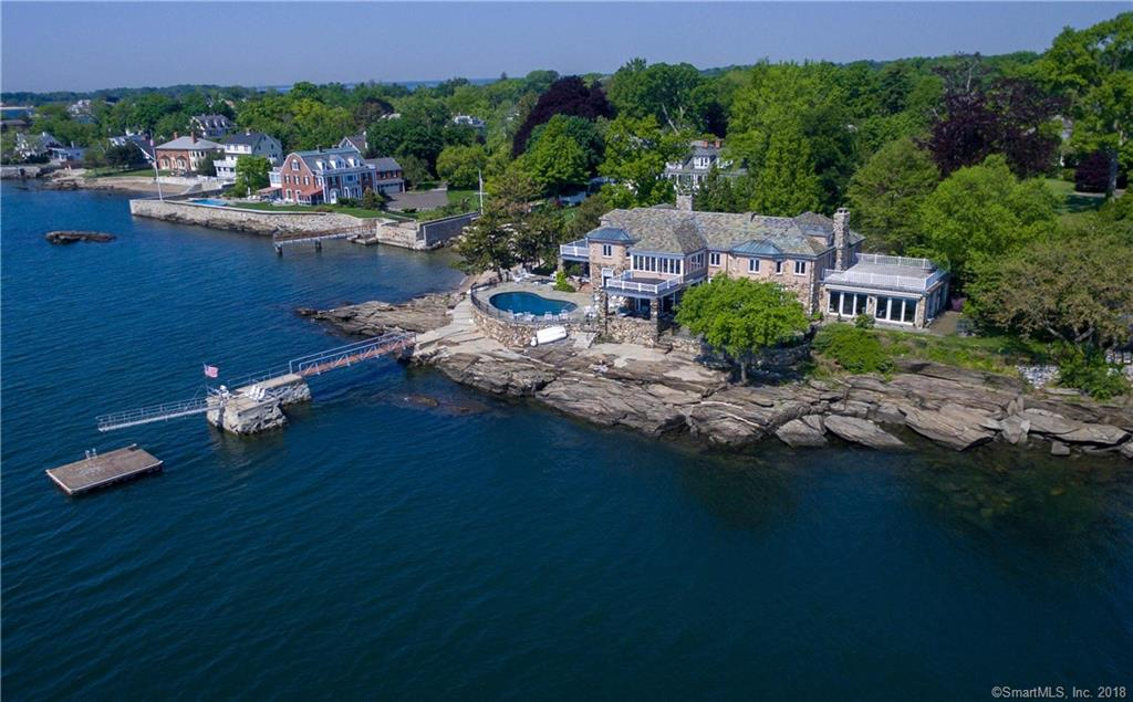 ''Rocklyn'', a direct waterfront ''Great Estate'' sited on spectacular high setting on coveted private lane. Unrivaled panoramic views of LI Sound, 235 ft of shore line, 45-foot pier with deep water mooring and pool with spa. This impressive sun-filled fieldstone manor, is perfectly maintained and designed for maximum enjoyment of a breathtaking seascape w/main floor rooms opening to a variety of open & covered waterfront terraces and  porches. Exquisite architectural detail; high coffered ceilings; 5 fireplaces. Grand living room leads to glorious sun room w/wet bar; elegant dining room; 3-exposure library. Separate staff wing.  Water views  from almost every room. Thoughtful restoration included dramatic family room off kitchen.  Once in a lifetime opportunity to acquire one of the original coastal estates in Greenwich.
