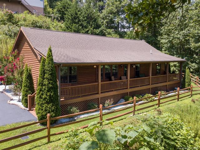 A Dream come True! One level log cabin with all comforts of full time living; offering serenity and privacy.  Only 10 mins to shopping, 12 to I-26.  Accessed by public roads, shared, beautifully maintained, driveway (with 1 neighbor), very gentle drive to house.  Peekaboo all year round view could be opened up if some trees cut back. (they are on this property) Long covered front porch provides wonderful outdoor living space to enjoy the valley/mtn view. Back deck perfect for grilling, even room for hot tub.  Split brm plan, open indoor gathering space with nice sized kitchen Large eating/prep island.  Generous walk in closets in all bedrooms. Wood floors and rock fireplace w/gas logs in Great Room.  Original owners, only used for occasional getaway a few weeks of the year.  But very well maintained.