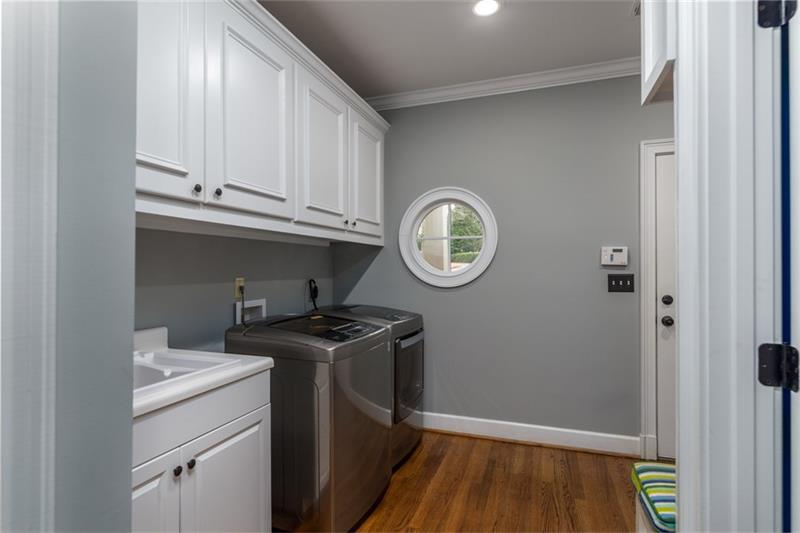 Spacious laundry room with plenty of cabinet storage & mud sink too!