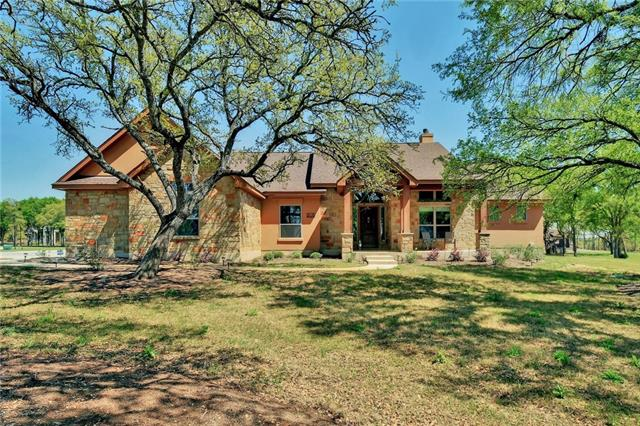 1-acre corner lot w/ mature oaks*Directly across from the community amenity center!WILLIAMSON County & Liberty Hill ISD*Private master bedroom & guest bedroom*Custom concrete floors*Family room boasts pitched ceiling w/ dramatic wood beams*Chic kitchen w/ built-in stainless appliances, travertine backsplash, farmhouse sink & pot faucet*Huge master showing w/ 7 shower heads*Built-in outdoor kitchen*Office*Secondary living/media room*Massive insulated 970 SQFT garage*HUGE backyard