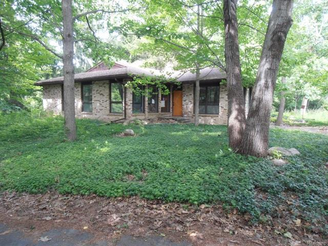 This is a Hidden Gem! It may be the last large, rolling, wooded parcel left in the western Detroit suburbs: 13 acres of Up North style peace & privacy, minutes from Detroit & Ann Arbor.  Better still, it boasts a sleek & lovely ranch home designed by the acclaimed mid-century modern architect, Tivadar Balogh. You'll find it on a designated Natural Beauty Road, nestled deep in the woods, with floor to ceiling windows to stream in the light & gorgeous leafy views. The modern & practical layout includes a large, open plan kitchen/dining/family room, living room, 4 bedrooms, 2 full baths,& a partially finished walkout basement. Original drawings for this home (and a 2-story version) are in the U of M Bentley Historic Library. There is a big old charming barn/garage for your vehicles, equipment, toys or a hobby farm too. 6 Horses/animals are allowed here, & the property can be split. A lovely stream & vernal pond meander across the north east corner. Don't miss out!