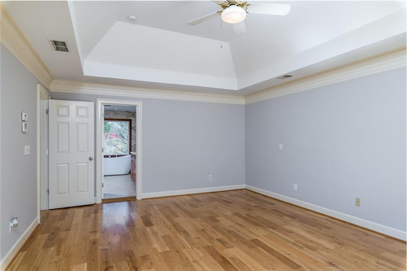 Spacious master suite with soaring trey ceiling & gleaming hardwoods!