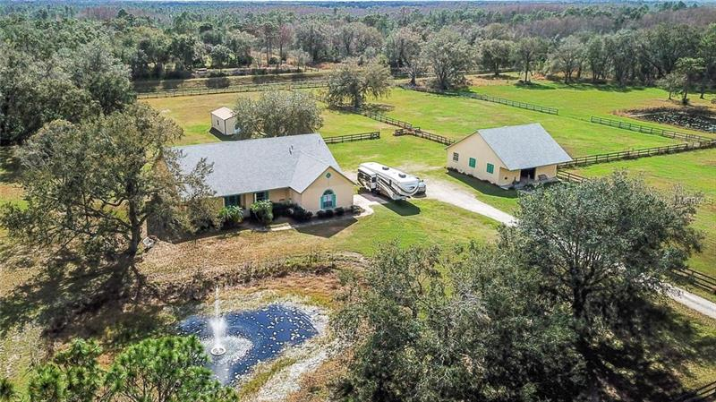 Expect to be impressed with this **ONE-OF-A-KIND EQUESTRIAN ESTATE HOME**! This extraordinary 12.5-acre Wedgefield hideaway surrounded by acres of wildlife preserves, parks, and lakes is only minutes from the beach and the Orlando Airport. This Wedgefield Horse Farm is located in a Golf & Equestrian community neighboring the 9,515 acre Hal Scott State Preserve presenting opportunities for camping, hiking, fishing, & nearly 16 miles of horse trails extending to the Econlockhatchee River. This luxurious property offers dramatic panoramic views of nature & local wildlife all throughout the home, adorned by mature trees, pasture lands, and a beautiful pond. Spacious open, airy interior creates a beautiful atmosphere featuring the finest architectural details and abundant windows to enjoy the serene views. **MODERN UPDATES INCLUDE NEW HOUSE AND BARN ROOF (2017) & UPDATED WATER HEATER** Your friends will envy the gourmet kitchen showcasing elegant cabinetry, breakfast bar, center island and **STAINLESS STEEL APPLIANCES INCLUDING A GAS RANGE**. The private master retreat delivers a beautiful scenic view, plus a master bath boasting dual sinks, a separate shower and a relaxing jetted tub to luxuriate in. Continuing quality spills from the inside out in this gated property containing 4 cross fenced pastures w/ water & a large 4 stable block barn surrounded by canal frontage on both sides. Have the fantastic fulfillment of living an alluring rural and convenient lifestyle in close proximity to everything you need!