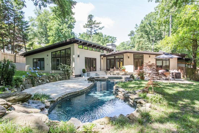 """Magazine worthy newly renov & expanded mid-century modern in Morningside. Dramatic sun-soaked open living w/high-end finishes, 15ft+ wood beam ceilings, 8"""" oak flrs, built-in walnut shelvng & custom lighting. State-of-the-art chef's kitchen w/10ft Michelangelo marble island & Miele/Subzero appl. Master wing w/walls of windows & dbl French doors that lead to rear garden/pool, marbled BA w/dual floating walnut vanity, soaking tub, heated floors & towel rack plus huge custm closet. Private guest suite & BA. Kid's wing has add'l 4BR/3BA.Seamless indoor/outdoor living. RARE!"""