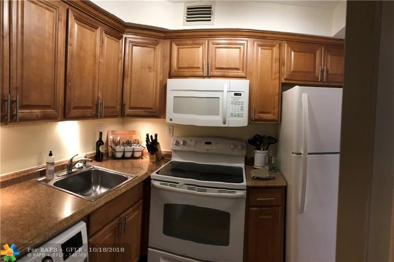 Investors-Rent immediately! Beautifully updated 1/1 waterfront, gated, pet friendly complex seconds from Wilton Manors.  Gorgeous kitchen, wood floors, impact windows and doors, instant heat hot water, washer/dryer in unit, huge walk-in closet, stunning bath, a screened patio with new flooring and freshly painted.  Amenities- a heated riverfront pool, tennis, storage, exercise room, clubhouse and a walkable dock with free boat dockage.  Maint fee of $258 includes reserves, cable, internet and water. Park right outside your door.  Motivated, qualify with 10%down.