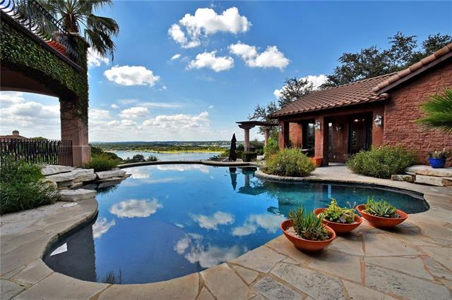 Drastically reduced for quick sale.  Owners are moving out of state.  Lake Travis waterfront Oasis on over 2 acres.  Private stone path to private, covered boat dock.  Two slips, one covered with lift.  Custom home designed by Jeff Berkus. Four bedrooms in main house, fifth in detached Casita.  Lake views from most rooms in the house.  Over 2000' of outdoor terraces.  Gorgeous pool looking out over the lake.  Guest house with kitchenette.  Elevator.