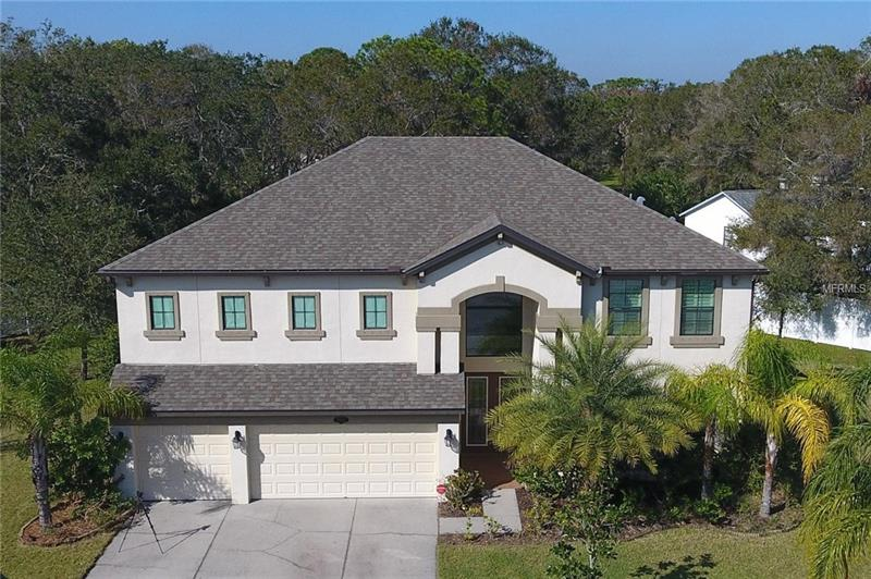 This fine Estate Home is located in the gated community of Heritage Reserve, conveniently located in the center of Pinellas County.  It offers over 3,800 Sq. Ft. of luxury living.  The gourmet kitchen features staggered cherry wood cabinets, granite counter tops, double oven and a convection microwave.  The center island makes a convenient work station.  There is also a walk-in pantry under the staircase.  The teen/mother in-law suite has a separate entrance to the pool, bathroom and kitchenette with sink and refrigerator.  Upstairs is a large master bedroom suite with spa-like bathroom featuring a separate tub and walk-in shower.  Slide the custom barn door open to see the bonus room.  It is currently being used as a media room and the large screen will remain with the home.  Push open the pocket doors in the family room to enjoy the outdoor living area.  A saltwater in-ground pool and custom outdoor kitchen are there for your entertainment.  Adding to your outdoor enjoyment is a fire pit and fish pond.  The very large, private yard has plenty of room for extra amenities.  This special home is in a non evacuation zone.  Alarm system, 3 car garage and so much more!