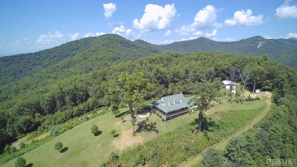 OWN YOUR OWN MOUNTAINTOP with 24 + Acres of pure privacy & a home with Breathtaking 180 DEGREE VIEWS of the Blue Ridge Mountains! Incredible Location, Nestled on the top of Keener Knob in WNC at almost 3500' elevation. Prepare to be overtaken by a sense of peacefulness as you enter the property, then relax on the wrap around porches where you can enjoy both Sunrises & sunsets + see the lights from downtown Franklin & the Fireworks from Highlands. Charming with character galore, 2 BR/2.5 BA retreat with spacious light-filled rooms, with lots of windows to take in the views from almost every room,+it has a bonus room that would make a great office + loft area too. Main level living with an Open floor plan, laminate wood floors, & dual CH&A. Outside there is plenty of flat area for gardens & has a double car garage, PLUS a Huge 46 x 36 commercial building that has both electric & water, it makes an awesome workshop, or store your RV, camper, or tractor. The 24 acres is unrestricted so keep all for yourself or sell off lots as it has already been subdivided & plated into a subdivision called Storch Summit Estates with roads going through it, that would be great for 4 wheeling.