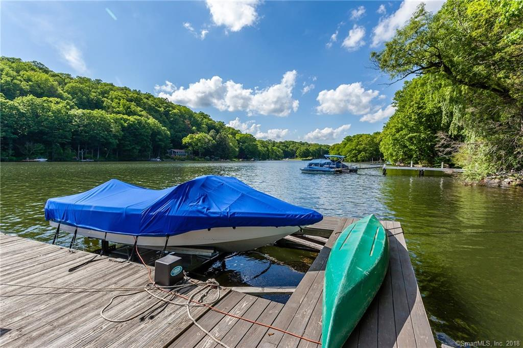 """150' DIRECT WATERFRONT - HOLIDAY POINT-A private Lake Community. Western Exposure. Perched in natural beauty w/one-of-a-kind private setting. Rustic water's edge cabana w/electric & water-huge level waterfront area and large c-shaped Dock & Lift. Huge tiered Deck. Totally modernized 1930's Contemp Chalet style home has a truly unique setting that offers privacy in the summer and sparkling panoramic water views in the winter. Vltd/beamed rustic FR w/stone frplc & skylight open to DR w/walls of windows. Updated Kitchen w/""""leathered"""" granite counters. Tumbled marble baths. Mst Suite w/private wrap Deck & wire railings. Special features include an Elevator for easy access to all 3 levels. Walk to community beach! A classic LAKE HOME!"""