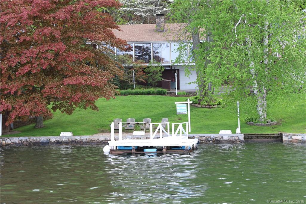 STUNNING WATERFRONT Ranch located on the point of Driftwood lake community with wide expansive panoramic lakeviews and level water frontage, with dock, lakeside patio, shed and mooring. The home has been lovingly maintained.  It offers of an open floor plan, dramatic cathedral ceilings, massive two sided fieldstone fireplace which opens to the eat-in kitchen and living room.  The large sunroom flows into the kitchen and living room with a wall of sliding glass doors offering expansive lake views.   The 2 spacious bedrooms have large windows that bring nature in, the bedrooms share a full remodeled bath with heated floor, towel heater & Bain ultra jetted tub. The lower level has a large guest room/family room with a full bath, laundry room and one car garage.  Located close to all conveniences of shopping and commuter routes.  Maintenance: furnace and a/c on annual service plan, septic pumped every other year, annual oil costs - budget 500 gallons/yr - cost $1239+- annually, summer electric bill June through September - $800+-, front roof in 2012, back roof 2015, new well pump 2015, new sea wall 2016 ($15k), floor-to-ceiling custom built shelving in living room, AC replaced in 2012, irrigation system, excavated and paved driveway on side of house - room to store a boat and still park 3 cars, paver sidewalk from drive to front door and back porch, stone retaining wall and back patio.