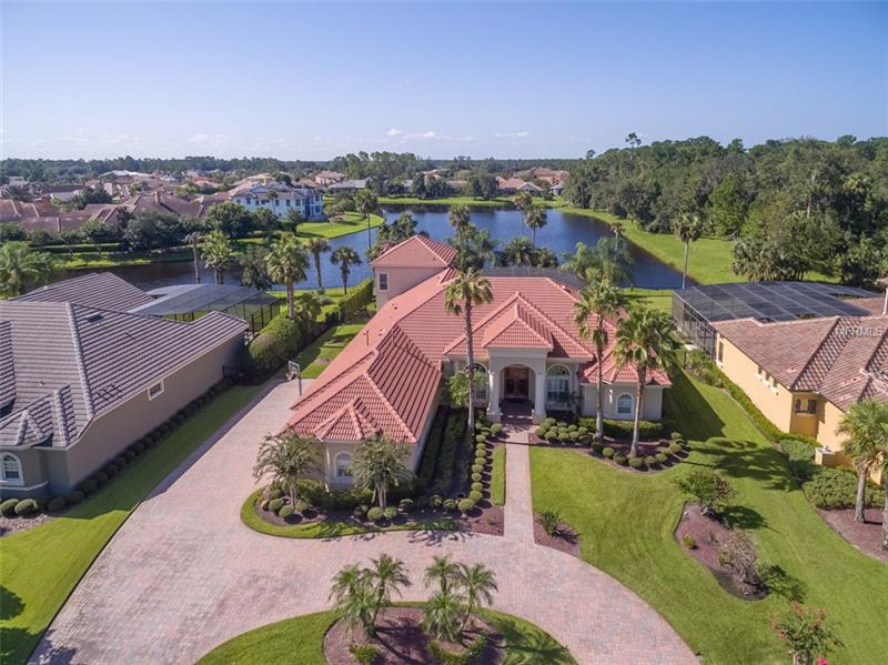 Beautiful guard-gated Alaqua Lakes home perfectly sited on one of the most desirable waterfront lots in the community! Florida Casual Living at its best with a welcoming entry with views of the tropical pool area backdropped by magnificent lake views. The foyer extends to the formal living room featuring a stone-cast gas fireplace and formal dining room with wood beam ceilings. Private study/office is located off the entry. The floor plan is perfect for family living and entertaining with 4 bedrooms downstairs and another bedroom upstairs currently used as a multi-purpose room along with a huge downstairs bonus room with wet bar located conveniently off of the pool area and outdoor summer kitchen. The kitchen consists of granite countertops, solid wood cabinetry, stainless steel appliances and a Viking 6 burner gas stovetop. The kitchen opens naturally to the family room featuring cathedral wood beamed ceilings. The master suite enjoys beautiful pool and water views along with his-and-her walk-in closets and master bath with dual sinks, garden bath and separate shower.   Alaqua Lakes is a 24-hour manned guard gated community with a 7 acre park, Pavilion, swimming pool, clay tennis courts, sand volleyball, basketball courts, playground & recreation field. Make this your home today and live the Florida lifestyle!