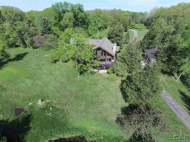 Appraised for $550,000. Captivating Landscape in the Heart of the Irish Hills. Water, water everywhere! Truly a Must See. Spectacular views from all rooms! Easily enough room for a Private Mother-In-Law Suite, 850' of lake frontage, boating, stream, pond and mesmerizing sunsets. Parking room galore for entertaining. Forested hills beyond lake are a sight to behold rich with wildlife. Fenced yard with two detached multi space garages. A wrap around wood deck for enjoying the outdoors. Inside you will find soaring ceilings with wood abounding elegantly finished. Superb family room with wet bar, living room with great stone fireplace, main floor master bedroom with full bath and super kitchen with dining area and finally first floor laundry await. Upstairs is large two bedrooms and full bath. Walkout huge partially finished basement. Third full bath in one garage. Additional 5 acres available!!!