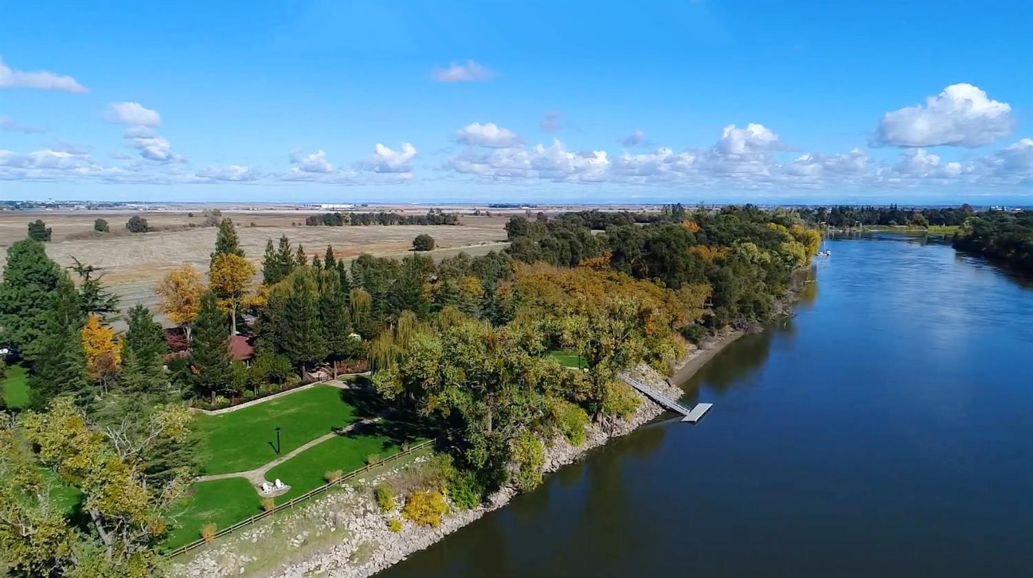 Considered the crown jewel of the Sacramento River, this prestigious waterfront estate w/ private boat dock is surrounded by spectacular vistas, nearly 2 acres of park-like grounds & superbly situated between tranquil county parcels, enhancing the expansive riverfront setting. The grand single story residence showcases a gracious Master St w/study, Library, 5 fireplaces, Guest Qtrs, pool & spa, port-cochere & 2 gated entryways.  Enjoy resort-style living, only minutes to Downtown & the Airport.