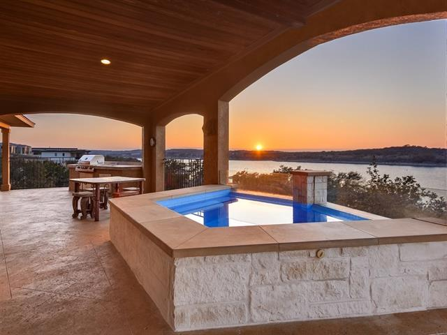 Lake Travis waterfront living at it's best! This well appointed lakefront home was constructed perfectly to capture every breathtaking view of Lake Travis from sunrise to sunset. Wall to wall windows in main living area looks out onto the expansive covered balcony that boasts a Jacuzzi spa and outdoor kitchen. Ground level covered patio offers a huge wet bar, fireplace and endless room for entertaining. Secret room w/ en suite, boat dock, two over-sized garages for large boat or RV are just a few more...