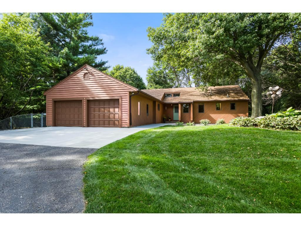 Beautiful 2.5+ acres of wooded privacy yet still close to schools, shopping & parks. RARE find in Shakopee. Walkout rambler w/ over-sized garage (32 ft deep), additional heated shop (24x36), open storage canopy, & storage shed. The yard has mature trees & is also fenced w/ a large wrap around deck on the backside of the home w/ gorgeous views. Impressive floor to ceiling brick fireplace is the focal point of the main level. Sunken living room, open floor plan, vaulted ceilings & well maintained.