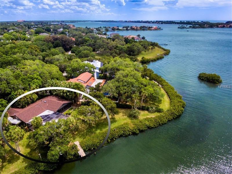 A SECLUDED & EXTRAORDINARY WATERFRONT LOCATION!  In a desirable mainland, bay-front comm.  w/ nearly three-quarters of an acre.  Extremely pvt w/ lush landscaping & mature oaks.  A diamond in the rough waiting to be polished until it shines.  The floor plan is comprised of 3 full bedrooms & 3 bath, including both a master & guest En Suite.  Characterized w/ vaulted wood ceil., skylights, track lighting, crown moldings, built-ins, oversized walk-ins, chair railing, mirrored walls, glass block, brick & parquet wood flooring, all well-preserved.  Remodel & conserve these affluent upgrades in an age gone by or explore possibilities of building new.  Multiple sets of sliding glass doors, clerestory & picture windows showcase the breathtaking water views.  The true nature of Florida living is captured outdoors on the screened lanai w/ a wood deck & a sparkling swimming pool overlooking the protected inlet (perfect for the personal boat dock) off of Little Sarasota Bay.  Pirate's Cove is one of Sarasota's coveted hidden bay-front gems.  The quaint neighborhood has less than 25 homes & features million-dollar properties melded w/ classic homes.  There are no association fees or restrictions, so bring your boat or R.V.  The 'West of Trail' address is nestled quietly w/ convenience to just about everything the Suncoast has to offer; including championship golfing, dining options, a myriad of shopping choices, downtown & area beaches like the number-one rated, white sugar sands of Siesta Key.