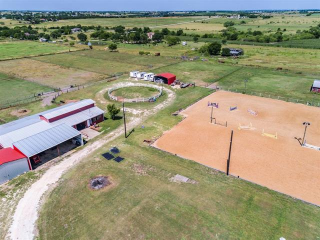Equestrian Property only 20 min to ATX! No restrictions - currently a horse boarding facility. 3/2 home is fully updated-energy efficient windows, granite, SS appliances & more! Workshop w/2 bays & 1/2 bath. Horse facilities w/11 stall, center aisle barn w/elect., water, tackroom, 3 wash racks, 3 cross ties & 8 cameras, 12'x12' stalls w/mats. Lighted arena w/crushed granite footing, lighted round pen, & 8 turnouts w/ troughs, 3 hay barns, pole barn & trailer parking. Coastal/bermuda hay field in front!