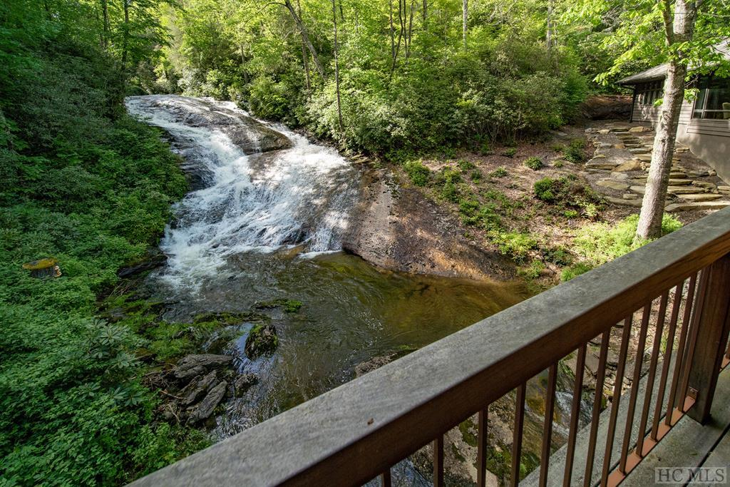 Straddling Knob Creek and a natural swimming hole, this one-of-a-kind 6,000+ square foot home looks into a series of magnificent waterfalls. The creek flows gently through the property with plenty of acreage on both sides for complete privacy. The long gated driveway is flat and meanders through sunny meadows and a lush forest. Deer and turkey frequent the fields and sometimes even elk pass through. With walking and four-wheeling trails, three ponds with a fishing dock, and an abundance of native flora and fauna to appreciate, there is always something fun to do.  The home itself is designed to offer relaxing views and sounds of the waterfalls and stream below from almost every room. A covered deck and huge central porch with fireplace and grill offer wonderful spots for listening to the water cascading over the rocks and taking in the incredibly beautiful surroundings. An instant stress reliever!  Since Mother Nature has provided the artwork, the interior has been fitted with an abundance of wide, floor to ceiling windows throughout. Reclaimed wood, vaulted beamed and trussed ceilings and fine stonework highlight the superior architecture and construction. With premium appliances, generous cabinetry and a large island with seating, the gourmet kitchen is a popular central gathering place — perfect for enjoying a quick breakfast or preparing food for a party. The master suite is a retreat all its own, with a sitting area, divine custom walk-in closet and spacious bath. Several guest rooms, a bunk room for the kids, fitness room, and TV/game room with mini kitchen round out the family-friendly floor plan.  With over 73 acres of enchanting grounds and a luxurious home with water features never to be duplicated, this remarkable estate must be seen to be fully appreciated.