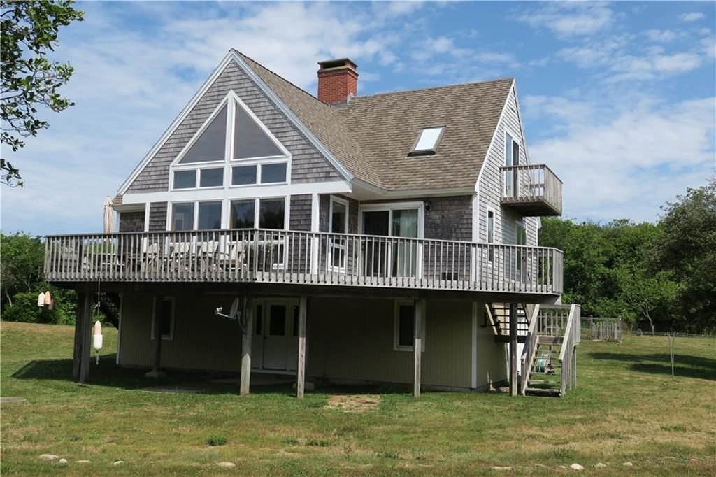 Private setting off Corn Neck Road for this attractive, contemporary Block Island home.  Spacious interior welcomes you in to a  cathedral ceiling living room with Vermont Casting Defiant woodstove, dining area with sliders to large deck spanning the front and side of house and cook's kitchen.  Half bath and master bedroom, walk in closet and full bath complete the second level.  Third floor has two large bedrooms and a full bath.  Lower level has attractive den, laundry room, hall entry and garage.  Set on a hidden 2.9 acre lot but close enough to walk to Mansion Beach.  Pride of ownership evidenced by these original homeowners.