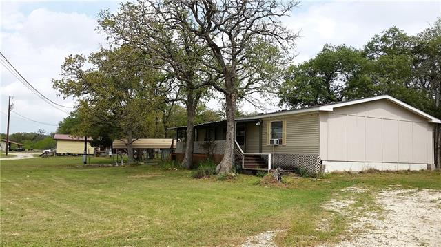 12.6 acres with 2 homes privately located in Cedar Creek,TX, a 3 bedroom, 2 bath double wide manufactured home with a large covered front porch, clean interior and lots of natural light. There is an additional 2 bedroom, 1 bath guest house with a cute kitchen. Beside the guest house are concrete runners from a previous DWMH. Further back on the land is a workshop with a covered parking area. There are two septic systems and separate meter loops at the houses. This property has lots of possibilities.