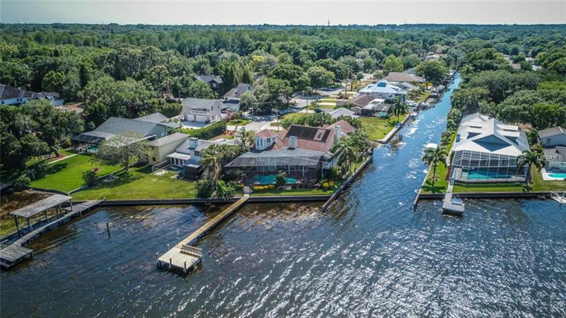 Epitomizing the Florida Lifestyle. Incredible, panoramic water views, sweeping ceilings and modern updates describe this opportunity. NEW ARRY'S ROOF AND BALCONY JAN 2018. When you enter, the Great Room just might take your breath away. The huge space, two-story ceiling, wall of windows overlooking Lake Tarpon. This spectacular room serves as the center of home for gathering, entertaining or just relaxing after a busy day. The kitchen is large with desk, pantry, island and an abundance of cabinetry. Dine elegantly in the Formal Dining Room using your butler pantry for preparation and serving. Perhaps you'd prefer to relax in the Library/Den, 13' x 34' adorned with book shelves and overlooking the Lake. Upstairs overlook the Great Room. The Master Suite has a balcony overlooking the Lake and brand new huge Bathroom. The Closet with built-in shelves/drawers is a room all to itself. Bedroom two is also large, 13' x 34' with walk in closet and bathroom. Bedroom three has a private staircase, high peaked ceiling and huge space with closet and bathroom. Don't miss the wine storage room on the way up. Step outside to an oasis of boating, fishing, swimming and more. Your private dock on the Lake, plus davits located on the canal running the side of the home offer perfect boat storage and launch areas. The screened pool/spa overlook the Lake. No representation to Pancake AC at the bar. Windows as is, some new, some not new.