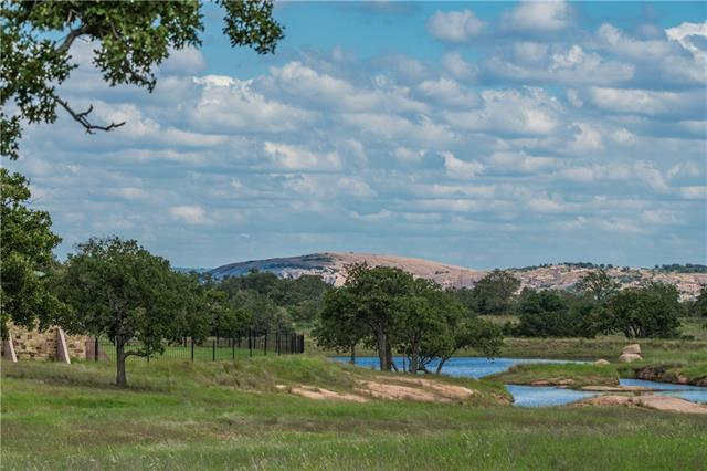 Maticulously renovated ranch overlooking Enchanted Rock. 4,610 sqft custom home: great room w/26' vaulted & beamed ceilings, kitchen w/mesquite countertops, custom bead board cabinetry, new exterior/interior paint, new concrete drive w/stained concrete porte cochere & lighted 4-car carport. 4,800 sqft Mueller steel bardomiunium w/1,760 square feet living quarters. New interior paint, windows. Main residence overlooks 2 ponds set amongst gently rolling coastal fields dotted w/striking granite outcroppings.