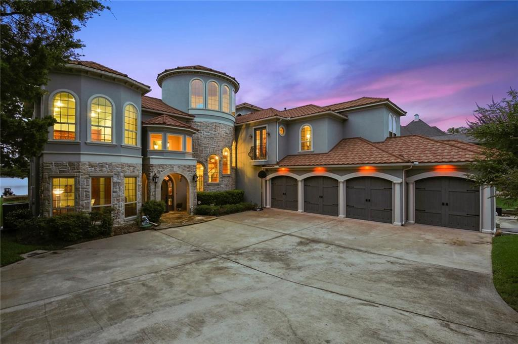 View the gorgeous sunsets while relaxing on one of the many balconies or decks on this exquisite lake front property!  This unique custom home features a private dock and slip with roof top deck, private hidden lookout tower, space for RV parking, 4 car garage with golf cart parking, garage built-ins, open office and study loft, hot tub, and game room.  As  you enter into this 5 bedroom masterpiece, you will be greeted with a grand staircase and cathedral dome ceiling, rich hardwood floors, and the beautiful water scenery throughout the many floor to ceiling windows.  This private lake and golf community is close enough to the big city to take the boat out for a weekend getaway.