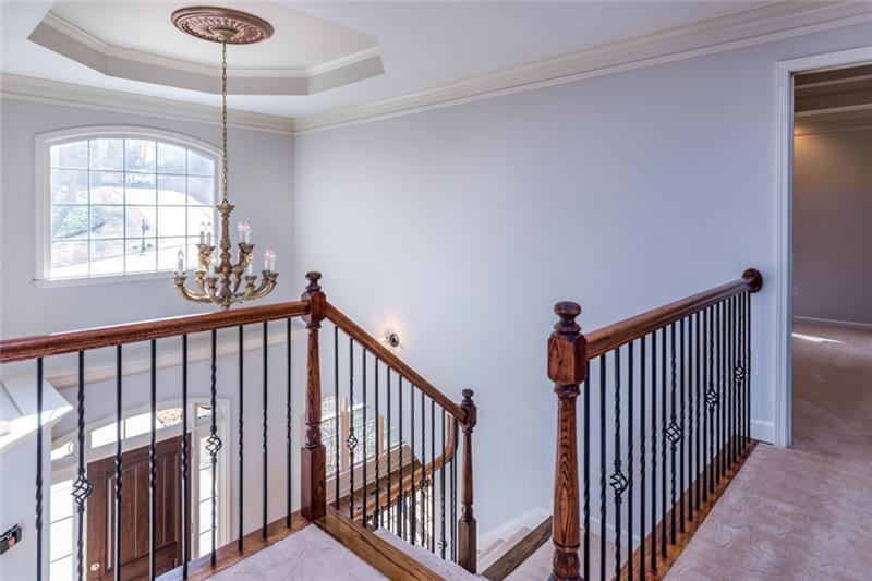 Upstairs landing overlooking gleaming foyer, accented by gorgeous wrought-iron spindles!