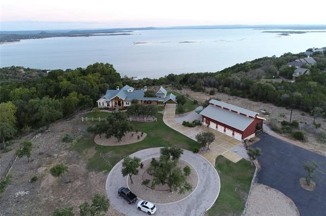 Stunning gentleman's ranch perched on 1 of the highest points in Burnet County w/PANORAMIC lake views, an exquisite former Parade home, & the most amazing car barn imaginable! Ag & wildlife exempt, this spectacular property boasts sky-high ceilings w/huge wood beams, gourmet kitchen w/ Thermador appliances,  3 BR/2.5B in main house, a private guest casita w/mini-kitchen & bath, & heated pool/spa. The jaw-dropping 2400SF htd/cooled 7-car garage has industrial car lifts, 1/2 bath, & huge workshop. MUST SEE!