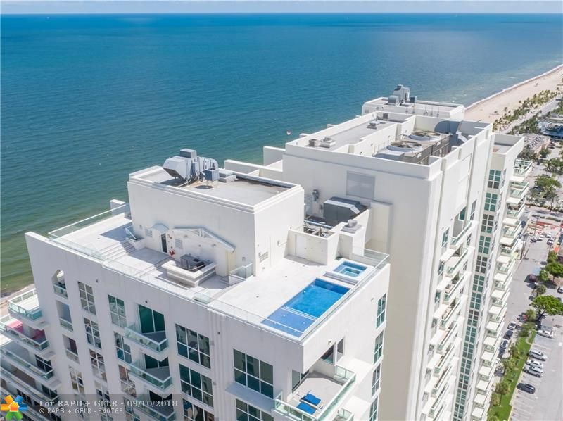 Direct Oceanfront! Imagine the combination of extraordinary Modern architecture with a privately deeded rooftop pool, spa, summer kitchen, bar & terrace capturing the ultimate ocean, city & intracoastal views! Private elevator access to your own roof top retreat.Custom floorplan: expansive open entertaining areas, chefs kitchen, private bedroom suites & entire Master Wing with over 2,000 sf of balconies & views from most rooms. Professional interior designer finishes. Resort quality full amenity building.