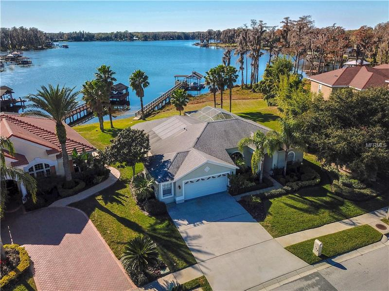 Aerial photo showing the home, rear dock and boat house, and Lake Osceola in the background.