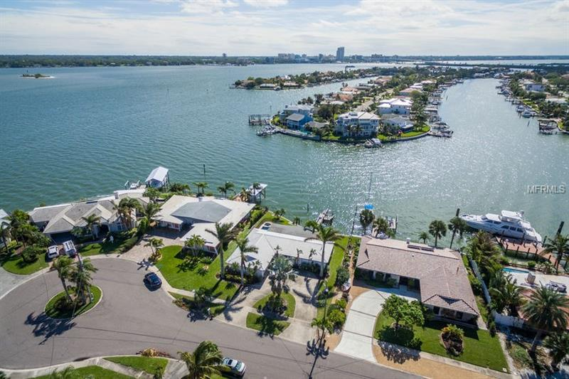 "LOCATION, LOCATION, LOCATION on exclusive Island Estates! Beautiful and unique waterfront views from whole house except bathrooms. Fabulous views in December of the Holiday Boat Parade & downtown Clearwater fireworks views from back yard waterfront. This home has a completely renovated kitchen overlooking pool and waterfront with open floor plan.  Florida room is not included in the square feet listed, needs A/C connection to increase square footage 288, for a total of 1,747.  Large sliding glass doors from kitchen & living room open into Florida room. Split bedroom plan, inside utility room, large walk in closet in master bedroom and hall walk in closet for extra storage. Newer waterfront pool has baby fence around it. Original features including bathrooms & windows so you can put your own renovation touch on. Island Estates has deep water surrounding a series of islands. Island Estates is a residential & shopping island community.  On the main island is casual & fine dining, large new Publix, shopping center, gas station, beauty salons, home to world famous Winter the dolphin at the Clearwater Marine Aquarium, PSTA transit & the Jolley Trolley.  Close to beaches and downtown Clearwater & SR 60 takes you directly to Tampa & Tampa International Airport.  House being sold ""AS IS"" only.   Your life is waiting make the move!"
