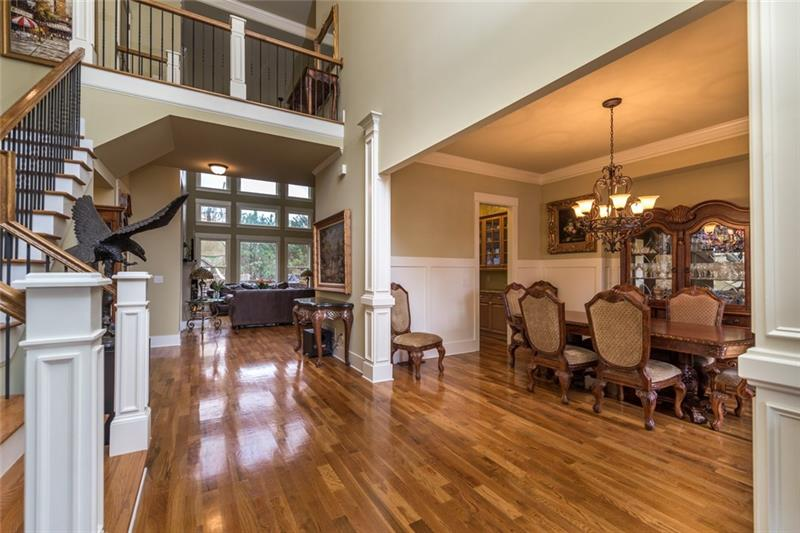 Two story foyer with hardwoods. Beautiful hardwood stairs with view of dining room.