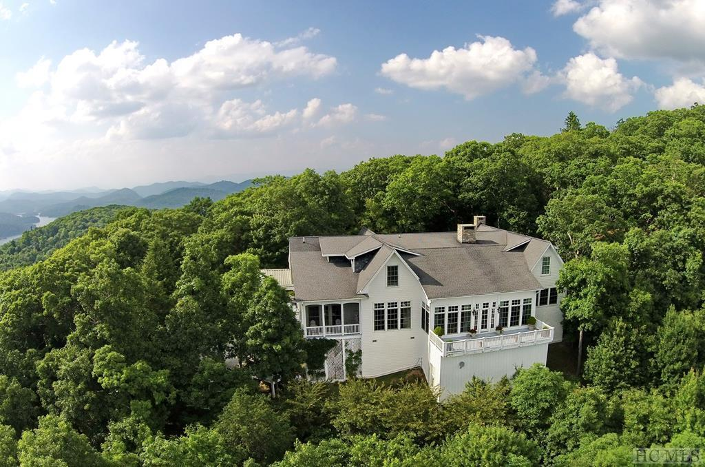 With exceptional architectural details and luxury finishes throughout, this elegant and inviting home is a must-see for those with discriminating taste and an appreciation for quality. Centrally located just minutes from the Cashiers Crossroads in the beautiful and private gated community of Big Sheepcliff, Aerie Manor was featured in Veranda magazine as one of the most astounding properties in the Western North Carolina mountains. Sitting at approximately 4,600 feet in a secluded setting, this estate is set amidst jaw-dropping panoramas of Cashiers, Cashiers Lake, and the multi-layered mountain ranges beyond.  Soaring 29-foot ceilings greet you at the entry and continue into the stately living area and sitting room. Filled with natural light, the living room floor-to-ceiling windows frame breathtaking views that go on seemingly forever. This stately home features two large master suites on the main level, and a pair of spacious guest suites on the upper level, each with its own private staircase. The expansive kitchen is a marvel unto itself, with two of every major appliance and plenty of counter space. Dine al fresco or in the formal dining room with its striking sandstone fireplace, just one of the several fireplaces throughout the home. Offered fully furnished, Aerie Manor is ready for its next owners to begin enjoying mountain living immediately.  The quiet gated community of Big Sheepcliff is just a short drive from the Crossroads. Enjoy shopping, dining, golf, hiking and much more in Cashiers and Sapphire, plus boating, fishing, waterskiing and swimming on beautiful Lake Glenville. Several country clubs are close by as well.