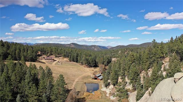 160+ contiguous acres potentially qualifying for landowner preference for hunting. Horse property, wooded, stunning rock formations & views on Bear Creek with a natural spring, ponds, multiple approved wells, livestock water tank, quiet private area that is surrounded by national forest land. Log cabin home with a full walkout out basement, wrap around deck with stunning views, bay windows, horse stable/tack room w/loft, 2nd kitchen in the basement, main floor office, slab stone kitchen counters, stainless steel appliances, 1000 gal propane tank, 20k watt back up electrical generator, wood burning fireplace, hardwood floors, security cameras around the property. 86 Hwy 67 parcel has a ranch style house 2,688 sq ft, wrap around deck, detached garage, pond, well, 2-500 gallon propane tanks. A hidden gem with Colorado mountain living and only about 30 minutes from Castle Rock & DTC. 6 parcels total.