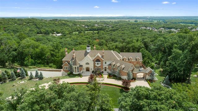 Located in the prestigious Upper Whitmoor Drive, you will find this beautiful blend of exceptional quality, regal details and magnificent finishes. This special estate is situated on 7 private acres with panoramic views of the Missouri River Valley. The artfully designed home and many garages comprises 25,000 square feet of total living space creating a unique opportunity to live in luxury while showcasing fine cars, boats or RVs. Upon entering the grand foyer, you will be greeted by a double sweeping staircase & immense 4,200+ crystal chandelier. The Neff designed kitchen features custom inlaid wood cabinets, granite counters, walk-in butler's pantry, adjoining breakfast room and hearth room. The master bedroom suite offers enviable views, luxurious bathroom & exquisite custom dressing room. The lower level offers a court for racquetball and basketball, gym & sauna. Commercial 15 person Otis elevator. Geothermal. Whitmoor Country Club has 36 holes of golf & more!