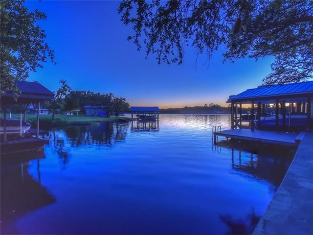 Beautifully updated 4 BR 3.5 BA one level waterfront home in coveted Blue Lake on constant level Lake LBJ. Sitting on approximately 1 acre in a park like setting w/ large live oak trees, this lakefront property has it all. Hot tub, fire pit, boat dock w/ deck above, oversized garage w/ walk up storage, and a separate heated and cooled room next to the carport that can be used as bonus space. Kitchen/dining area has solid granite counter tops, wood floor, and 10'ceiling with crown molding.