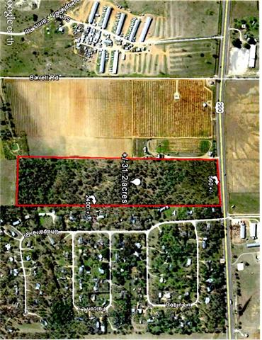 31.25 beautiful tree shaded acres with 500 feet of hwy 290 frontage in the heart of the Texas Wine Trail! Located 7 miles east of Fredericksburg's Main Street, across the road from Wildseed Farms and 3 miles west of Grape Creek Vineyard. Flat, fenced, and surveyed. Engineered plans available.  3 wells in place, and currently undergoing public water studies for future commercial use for one of the wells. Owner financing available.