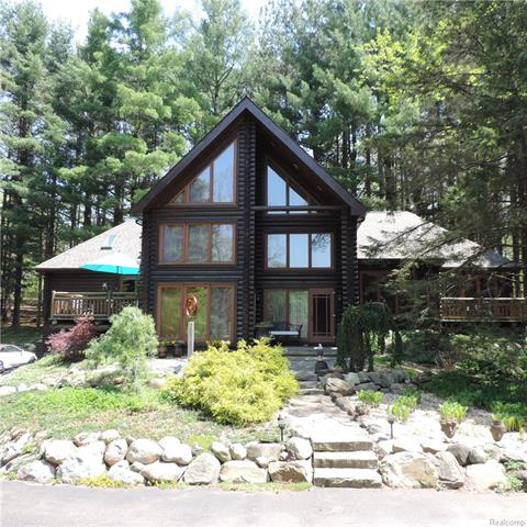 Own a northern Michigan custom log home and retreat close to home! Swim, fish, garden or hunt on your 21 acre estate with a private pond, shade garden, stone pathways, privacy berm, perennial gardens and breathtaking stand of white pines. Equestrian lovers will love the acreage. You enter into 2,909 square feet of custom home with rough hewn beams throughout, many of which were native to the property.  Enjoy the warmth of a new fireplace with remarkable stone hearth. The gourmet kitchen of your dreams awaits, offering Dura Supreme auto & soft close cabinets with pull outs & custom shelves. You'll be captivated by the sprawling counters of distinctive Marinace Brazilian granite and high end Sub Zero and Wolf appliances. Updated stylish master bath & first floor bath.  Enjoy peace of mind with a whole home generator. This home offers stunning architecture in a private nature setting with loads of desired amenities. Only 26 minutes to Great Lakes Crossing & 46 minutes to Somerset Mall!